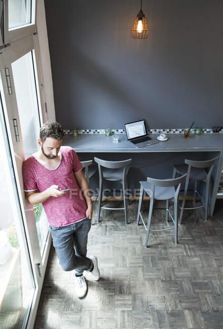 Junger Mann in einem Café mit Handy — Stockfoto