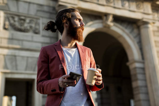 Hombre de pie con café y smartphone - foto de stock