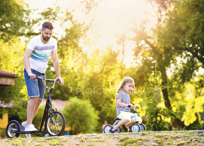 Pai e sua filhinha com carro de brinquedo e scooter em um parque — Fotografia de Stock