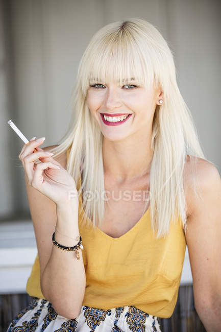 Portrait of smiling blond woman smoking cigarette — Stock Photo