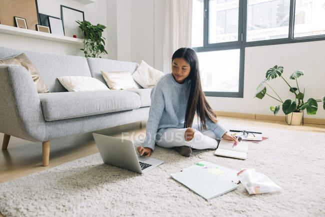 Femme assise sur le sol et à l'aide d'ordinateur portable — Photo de stock