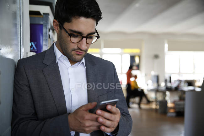 Бізнесмен, дивлячись на його смарт-телефону в сучасні офісні — стокове фото