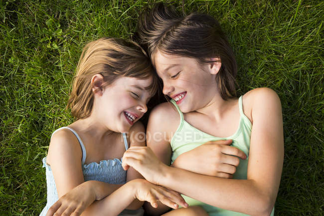 Two sisters lying on meadow and having fun — Stock Photo
