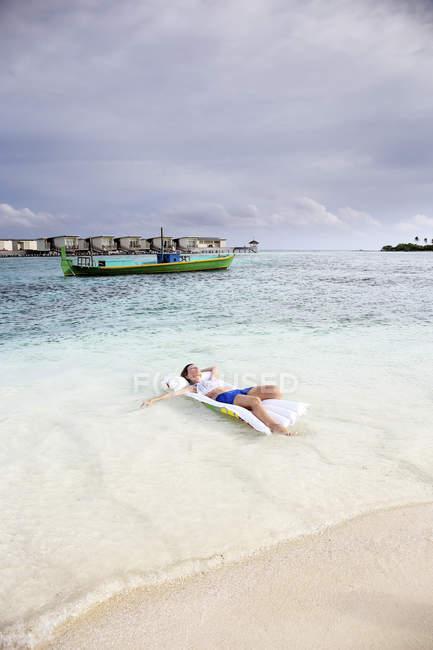 Мальдивы, Guraidhoo, женщина, плавающей на надувной матрац в мелкой воде — стоковое фото