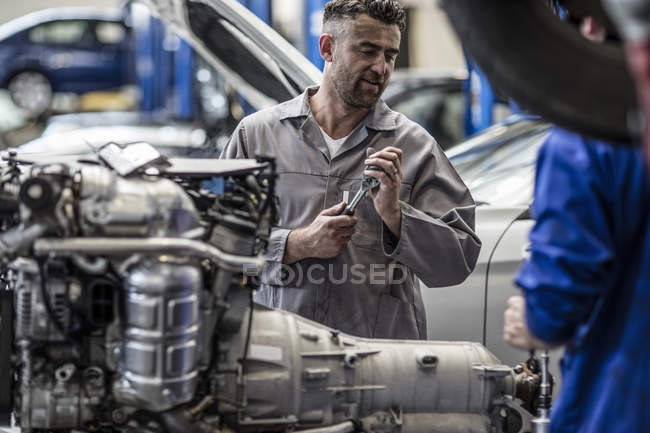 Two car mechanics next to v8 engine in a workshop — Stock Photo