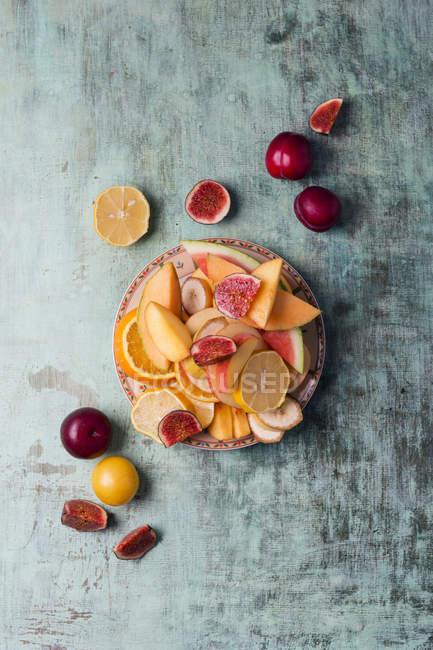 Блюдо с нарезанной дыней, инжиром, апельсином, бананом и сливами на серой потрепанной древесине — стоковое фото