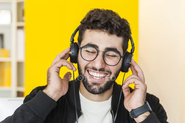 Portrait of laughing man listening music with headphones — Stock Photo