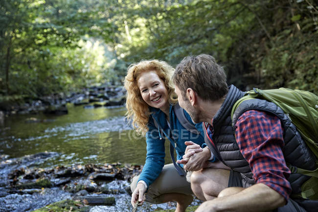 Couple hiking in forest, crouching at brook — Stock Photo
