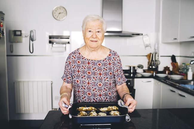 Ritratto della donna senior con cibi preparati in cucina — Foto stock