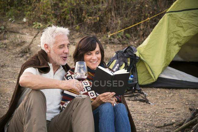 Casal sênior feliz com vinho e livro em uma tenda — Fotografia de Stock