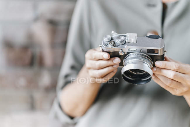 Female hands holding retro camera — Stock Photo