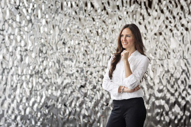 Portrait of confident businesswoman in front of rippled wall — Stock Photo
