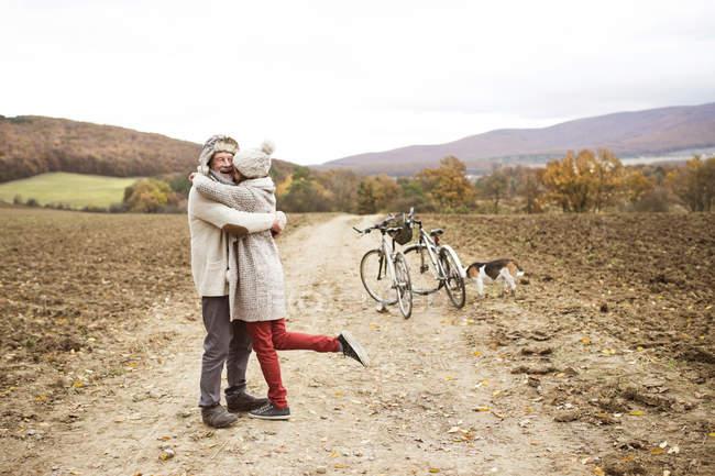 Coppia anziana che fa un viaggio in bicicletta con cane — Foto stock