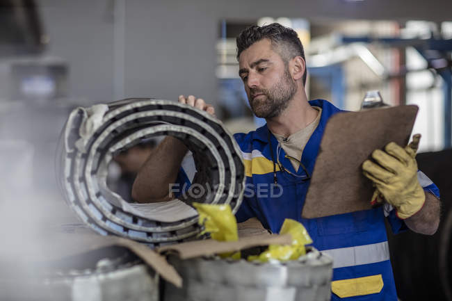 Worker taking stock with clipboard in factory — Stock Photo