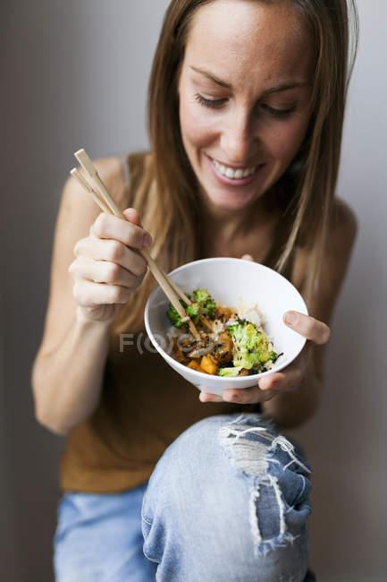 Frau zu Hause essen Gemüse mit Stäbchen — Stockfoto