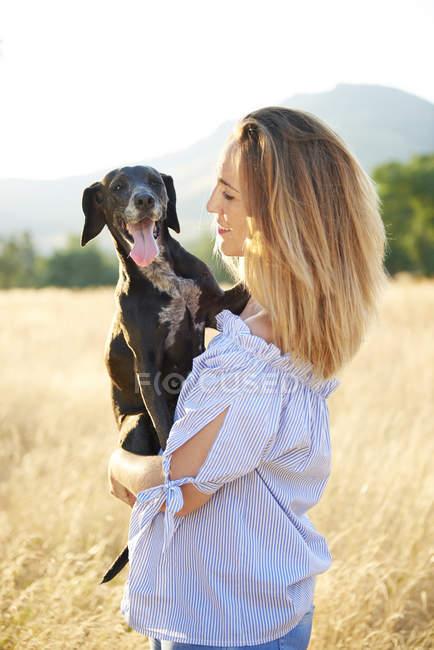 Mulher feliz com seu cão na natureza — Fotografia de Stock