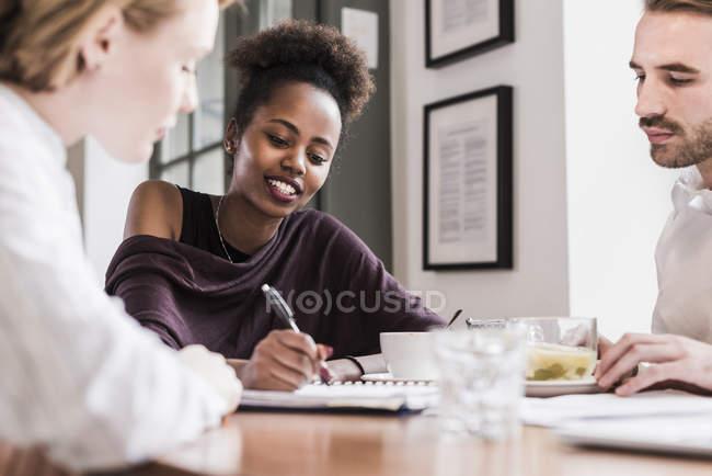 Трое молодых людей, работающих в кафе — стоковое фото