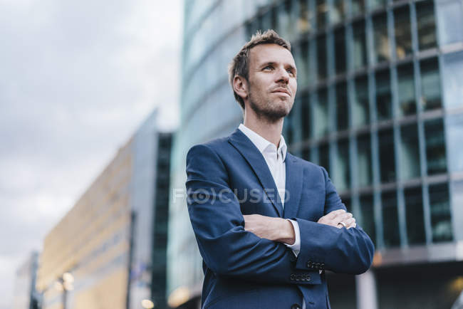 Portrait of businessman standing on street with arms crossed — Stock Photo