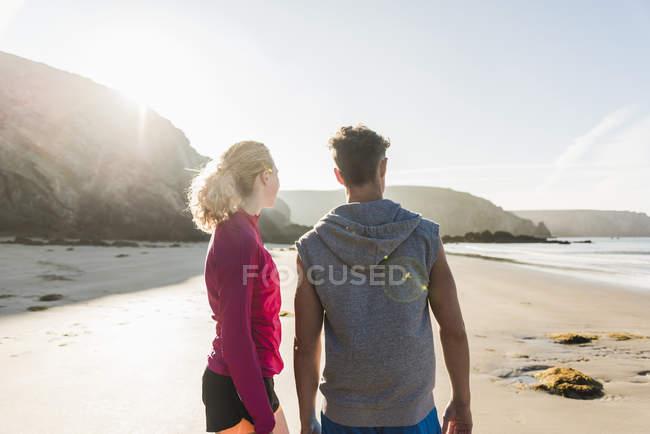 Vue arrière de standing sportif de jeune couple sur la plage, france, presqu'île de crozon — Photo de stock