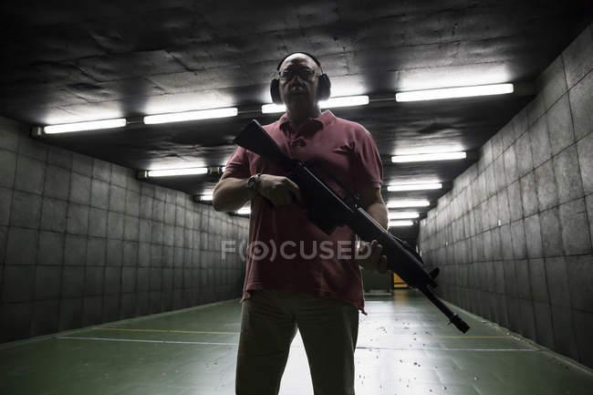 Homem segurando uma arma tática em um campo de tiro indoor — Fotografia de Stock
