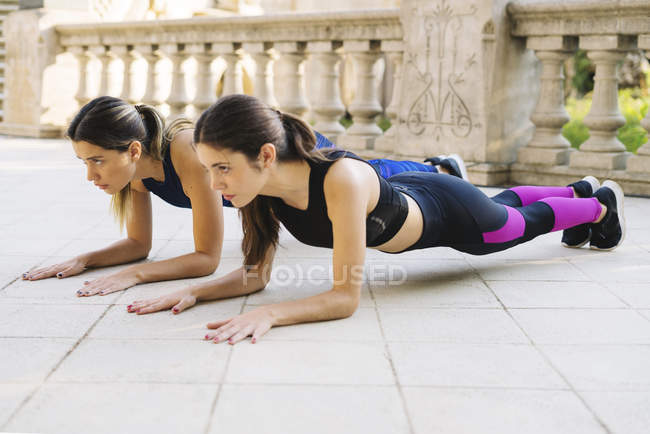 Two sportive young women exercising outdoors — Stock Photo