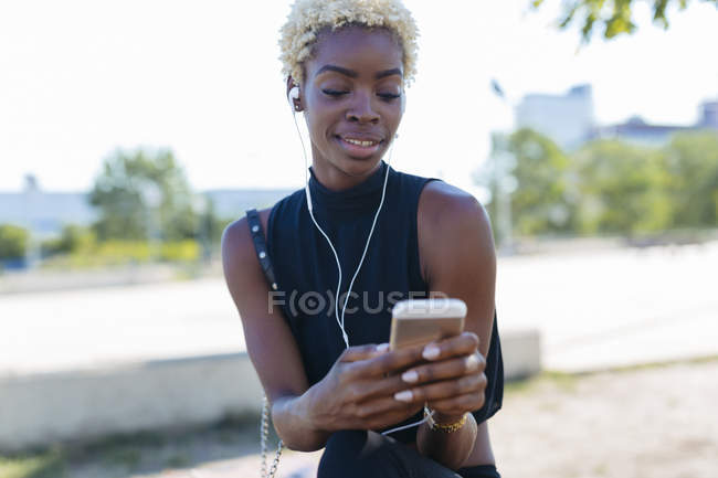 Smiling young woman with cell phone and earbuds sitting outdoors — Stock Photo