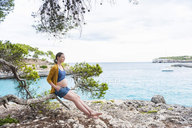 Pregnant woman sitting on branch at sea coast — Stock Photo