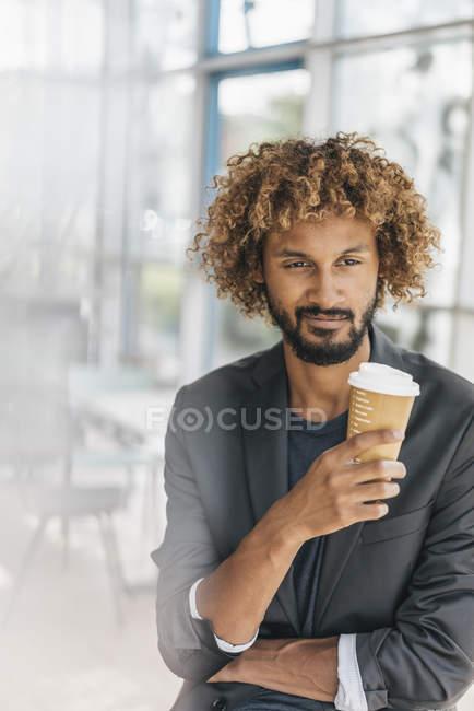 Jovem empresário beber café de copo descartável — Fotografia de Stock