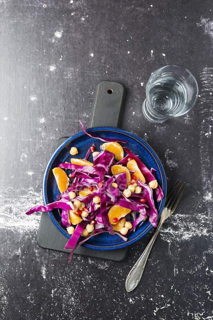 Wintersalat mit Rotkohl, Mandarine und Kichererbsen auf blauem Teller — Stockfoto