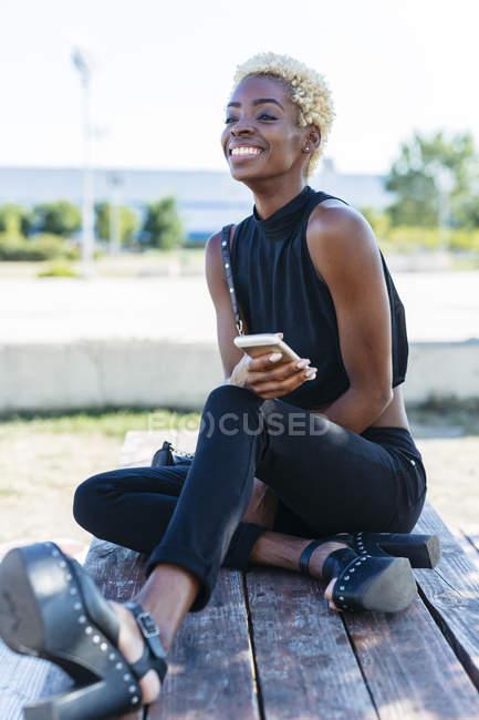 Lächelnde junge Frau sitzt auf Bank und hält Handy in der Hand — Stockfoto