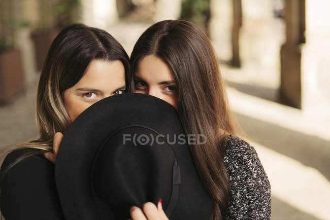 Deux meilleurs amis cachent leur bouche derrière un chapeau noir — Photo de stock