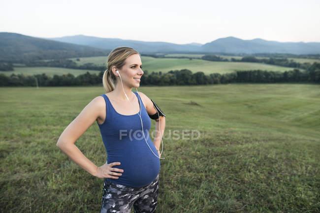 Jeune femme sportive enceinte écouteurs permanent à l'extérieur — Photo de stock