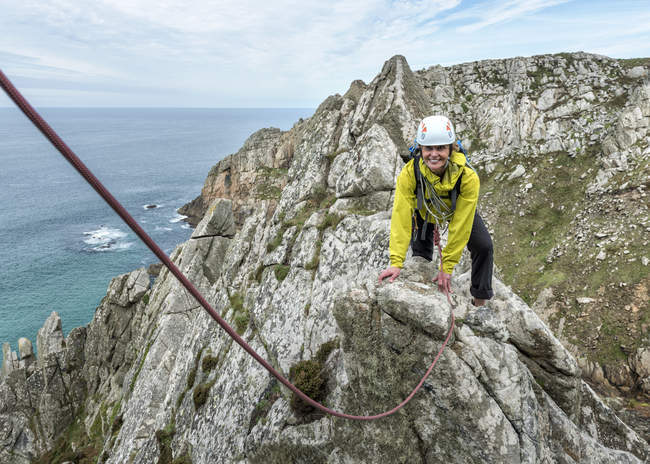 UK, Cornwall, smiling woman climbing on Commando Ridge — Stock Photo