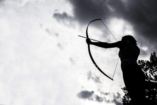 Silhouette of an aiming young sporty archeress — Stock Photo