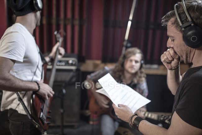 Rock band rehearsal in recording studio — Stock Photo