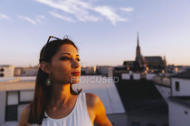 Austria, Vienna, young woman relaxing on rooftop at sunset with Stephansdom in the background — Stock Photo