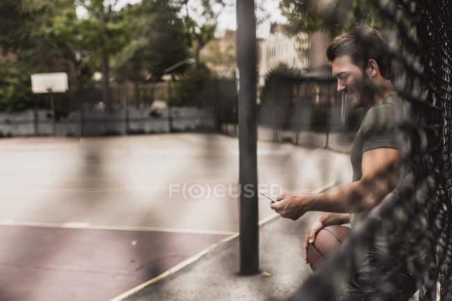Jeune homme avec téléphone portable et basket sur un terrain extérieur — Photo de stock