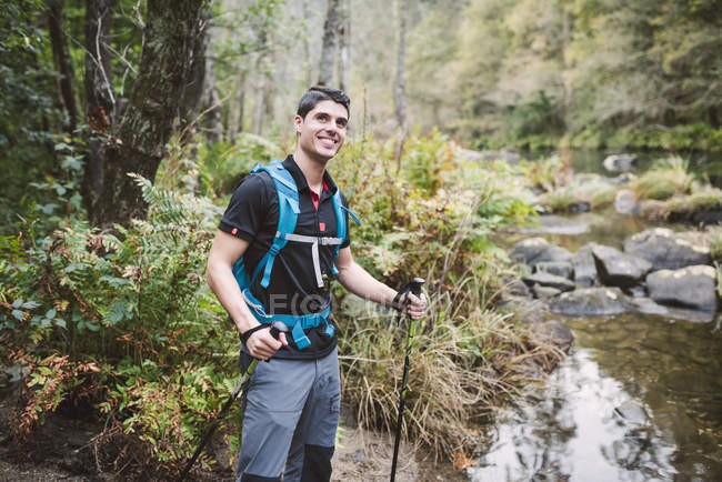 Escursionista sorridente in piedi sulla riva di un fiume — Foto stock