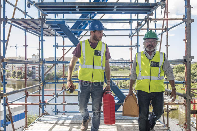 Construction workers on construction site carrying tool boxes — Stock Photo