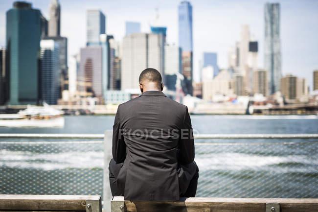 USA, Brooklyn, vista posteriore di un uomo d'affari seduto sulla panchina davanti allo skyline di Manhattan — Foto stock