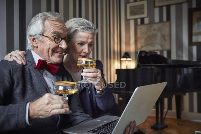 Happy senior couple drinking champagne and using laptop at home — Stock Photo
