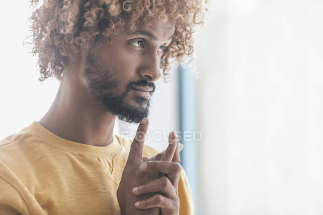 Pensive young man standing next to window — Stock Photo