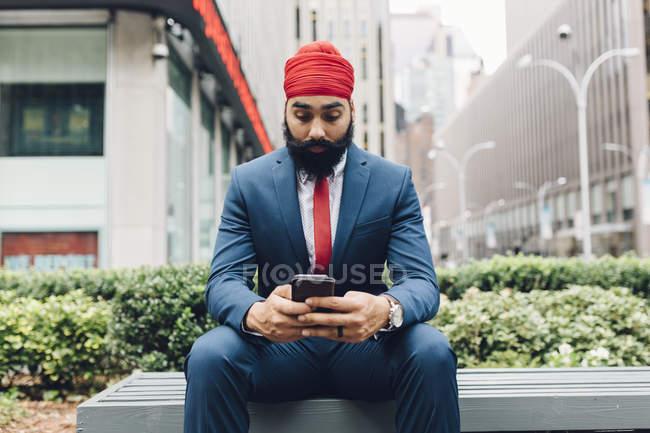 Индийский бизнесмен сидит на скамейке запасных и пользуется смартфоном в Манхэттене, штат Нью-Йорк, США — стоковое фото