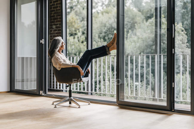 Woman with long grey hair sitting on chair in loft — Stock Photo