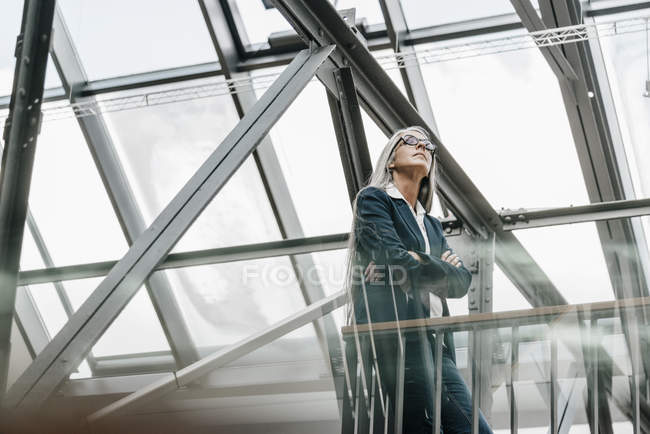 Woman with long grey hair standing in loft — Stock Photo
