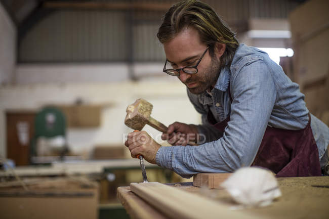 Craftsman in eyeglasses working in wood work — Stock Photo