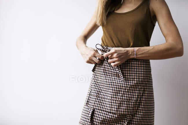 Mujer atando alrededor de delantal - foto de stock
