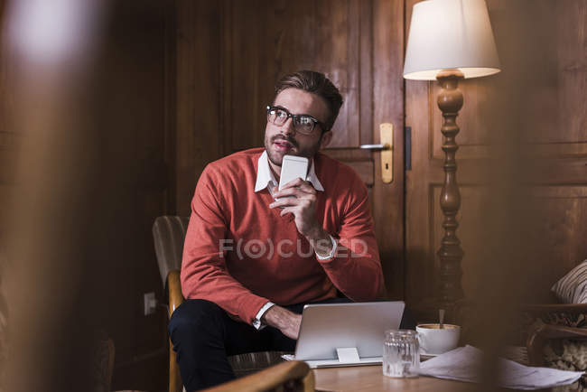 Young man with cell phone and tablet sitting in a cafe — Stock Photo