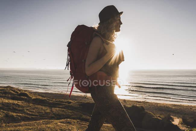 Ragazza adolescente bionda con zaino che cammina sulla spiaggia la sera crepuscolo — Foto stock