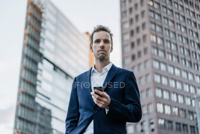 Портрет бизнесмена со смартфоном, стоящим в городе — стоковое фото